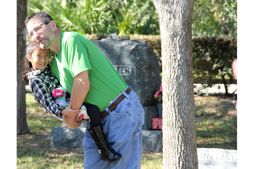 Tony MacDonald scoops up his daughter Elizabeth at the Hillside Cemetery on Saturday, March 4. Photo by Jacque Estes