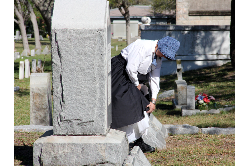 Caroline Carnell adjusts her costume by her family'  s grave at Hillside Cemetery. Photo by Jacque Estes