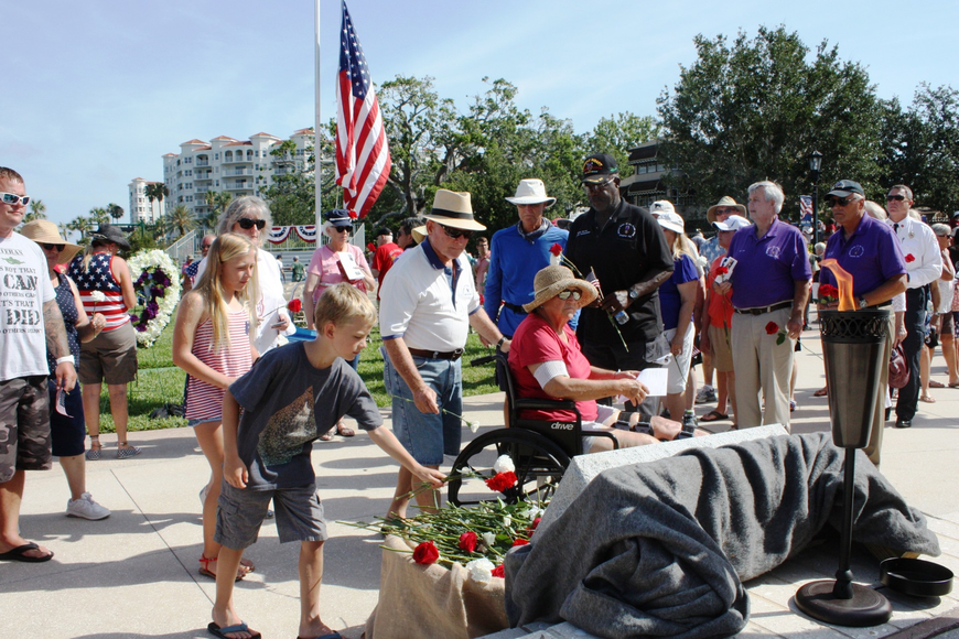 Those attending were given carnations to drop by the eternal flame. Photos by Wayne Grant