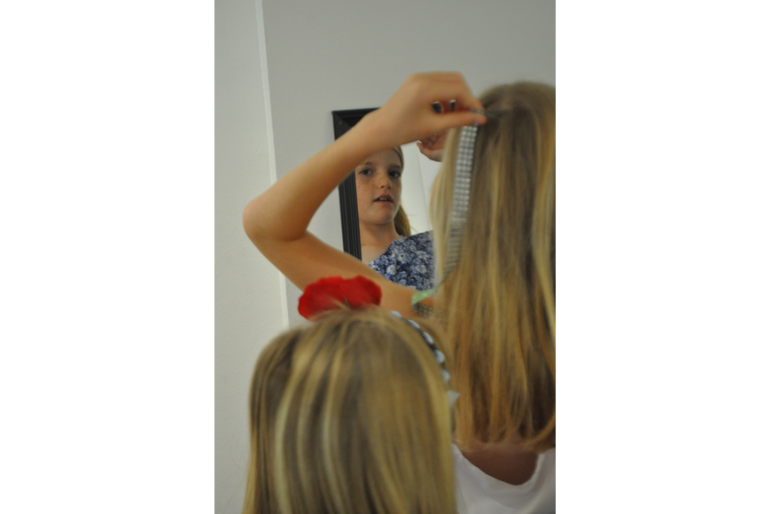 Brooke Hoobler, 8, adjusts herself in the mirror before the Fashionista Camp Fashion Show on June 30, at the Ormond Memorial Art Museum.