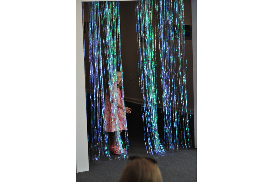 Ella Pender, 6, peeks out of the shimmering curtain during the Fashionista Camp fashion show on June 30, at the Ormond Memorial Art Museum.