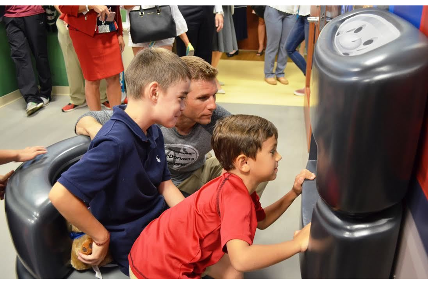 Alec Riley, 9, of Palm Coast (blue shirt), and Maxwell Chacon, 5, of New Smyrna Beach (red shirt), play video games with NASCAR driver Jamie McMurray in the hospital's new playroom. Courtesy photo