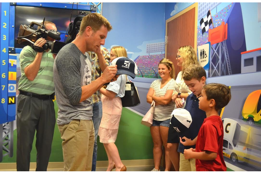 Jamie McMurray autographs hats at the dedication of the new pediatric area at Florida Hospital Memorial Medical Center. Courtesy photo