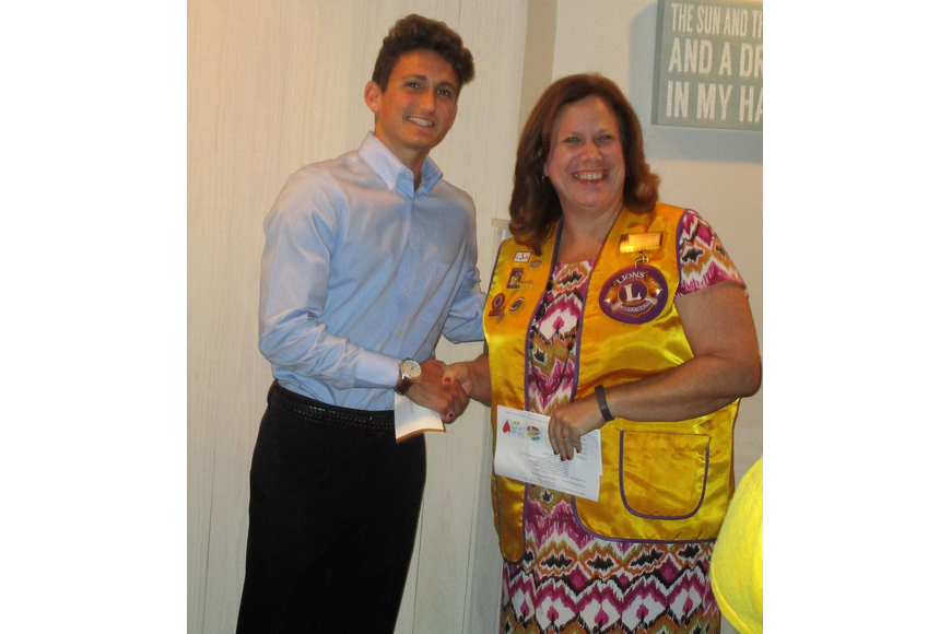 Scholarship Committee Chair Lion Linda Koch presents a scholarship check to Cody Carrier. Courtesy photo