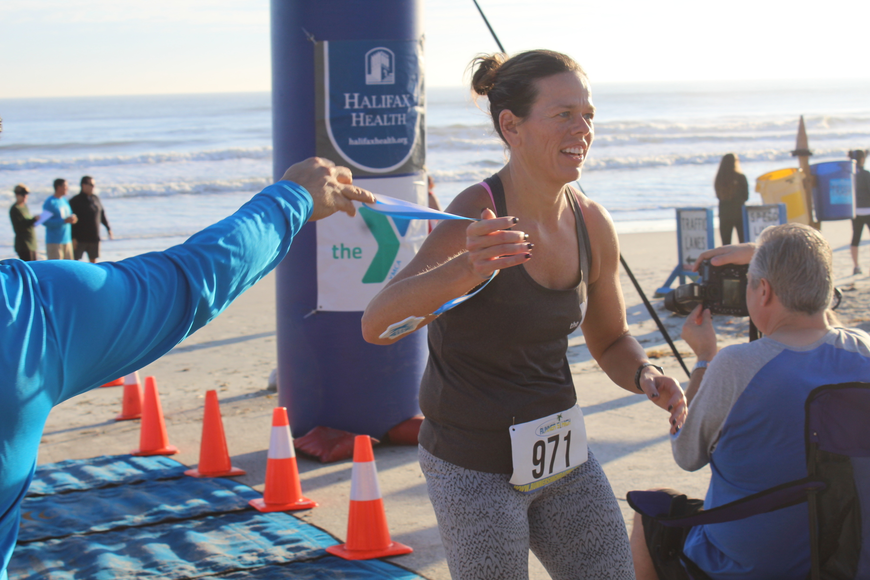 YMCA Special Events Director Mica Lill crosses the finish line at the Ormond Beach Family YMCA Polar Plunge 5K on Saturday, Dec. 2. Photo by Jarleene Almenas