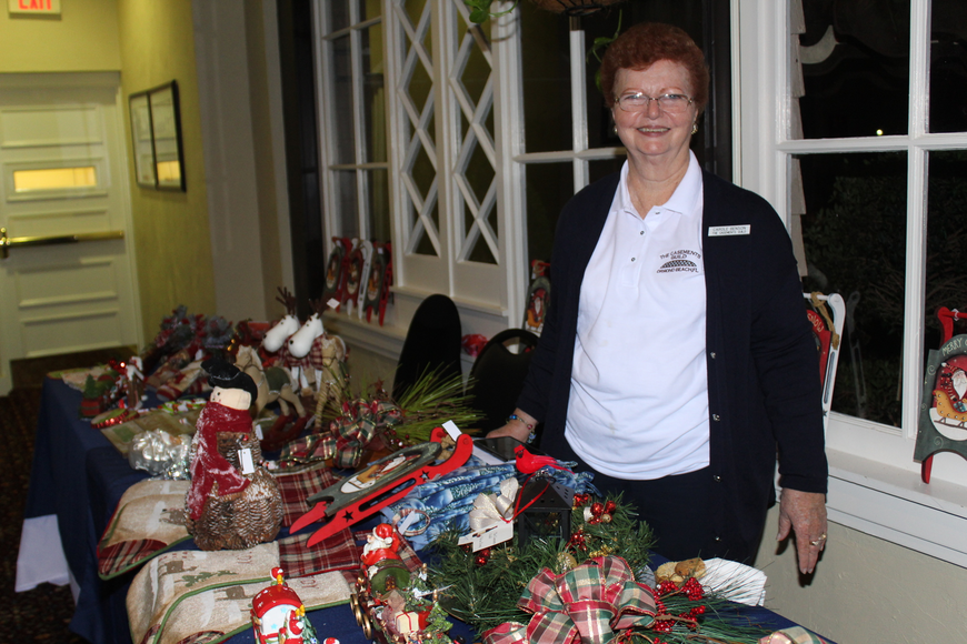 Carole Benson of The Casements Guild smiles behind a table of Christmas ornaments during the 29th-annual