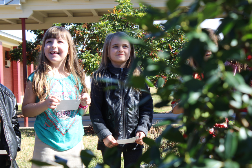 Adeline Fela and Aurya Simpson listen happily during the holly tree donation on Jan. 19. Photo by Jarleene Almenas