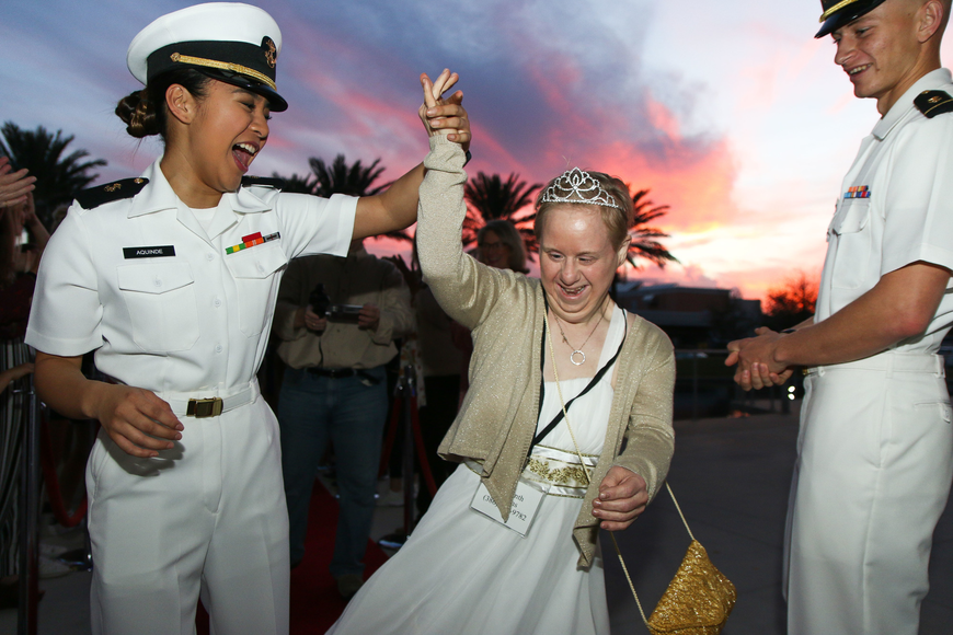 An Embry-Riddle Navy ROTC student twirls Lisa Strocky, of Lake Helen, on the red carpet. Photo by Paige Wilson
