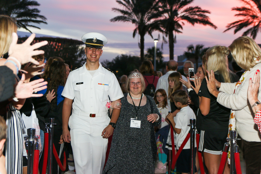 An Embry-Riddle Navy ROTC student escorts Carla Lusk, of Lake Helen, down the red carpet as volunteers welcome her with enthusiasm. Photo by Paige Wilson