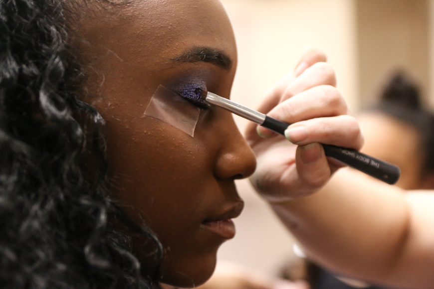 KEDA Assistant Director Sarah Smith applies glitter to Sanah Spar's eyelids before the show. Photo by Paige Wilson