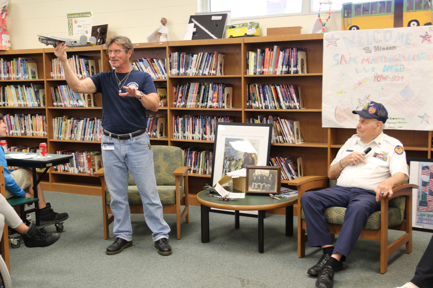 Hinson Middle School teacher Joseph Vetter holds up a B-24 aircraft model as WW2 veteran Sam Mastrogiacomo tells his story on Friday, April 13. Photo by Jarleene Almenas