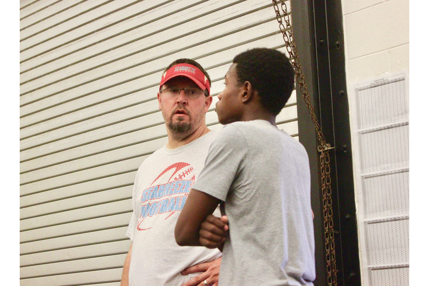 Seabreeze coach Troy Coke gives advice to a player during the lifting portion of workouts. Photo by Ray Boone