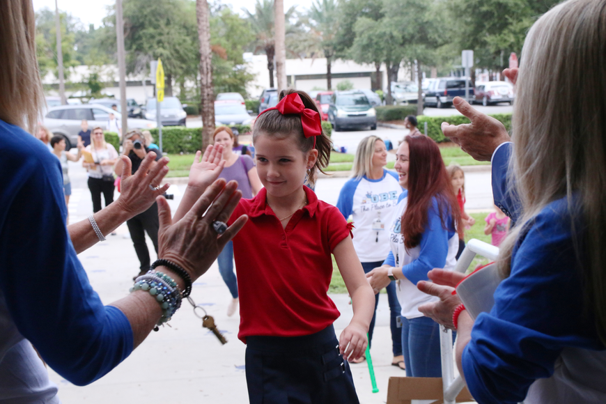 Olivia Sessions high-fives school staff as she enters the building on the first day of school at Ormond Beach Elementary on Monday, Aug. 13. Photo by Jarleene Almenas