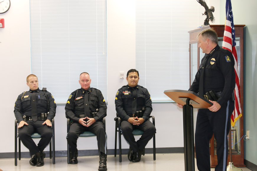 Detective Sgt. Michael Garner, Cpl. David Lank and Cpl. Jay Brennan listen as Police Chief Jesse Godfrey speaks during their promotional ceremony on Friday, Aug. 24. Photo by Jarleene Almenas