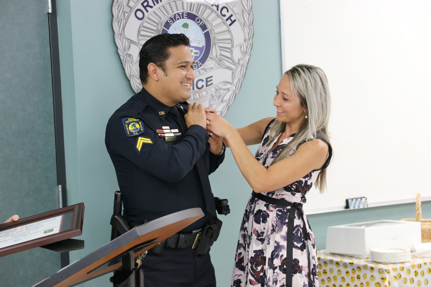 Rebekah Brennan pins a badge on her husband, Cpl. Jay Brennan, during his promotional ceremony on Friday, Aug. 24. Photo by Jarleene Almenas