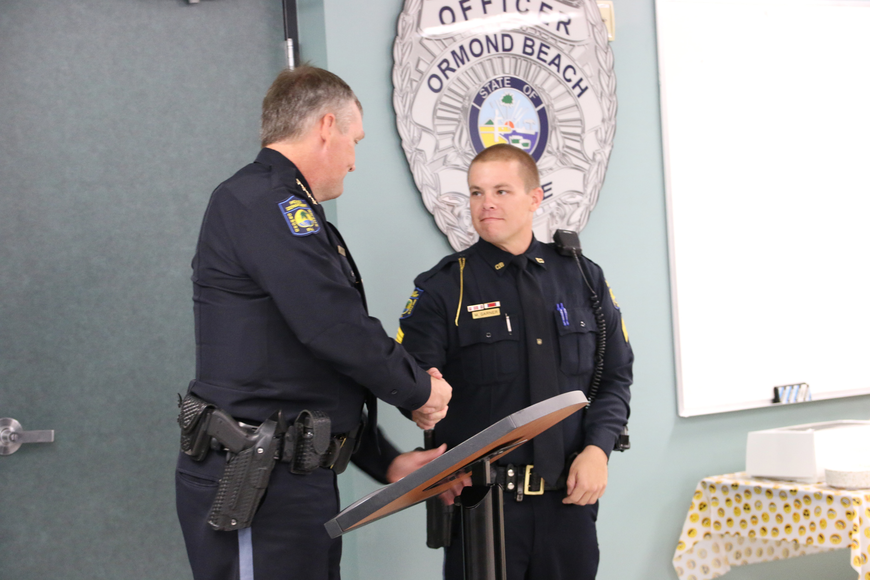 Chief Jesse Godfrey shakes Detective Sgt. Michael Garner's hand during his promotional ceremony on Friday, Aug. 24. Photo by Jarleene Almenas