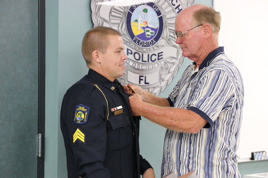 Detective Sgt. Michael Garner has his badge pinned by his father during his promotional ceremony on Friday, Aug. 24. Photo by Jarleene Almenas