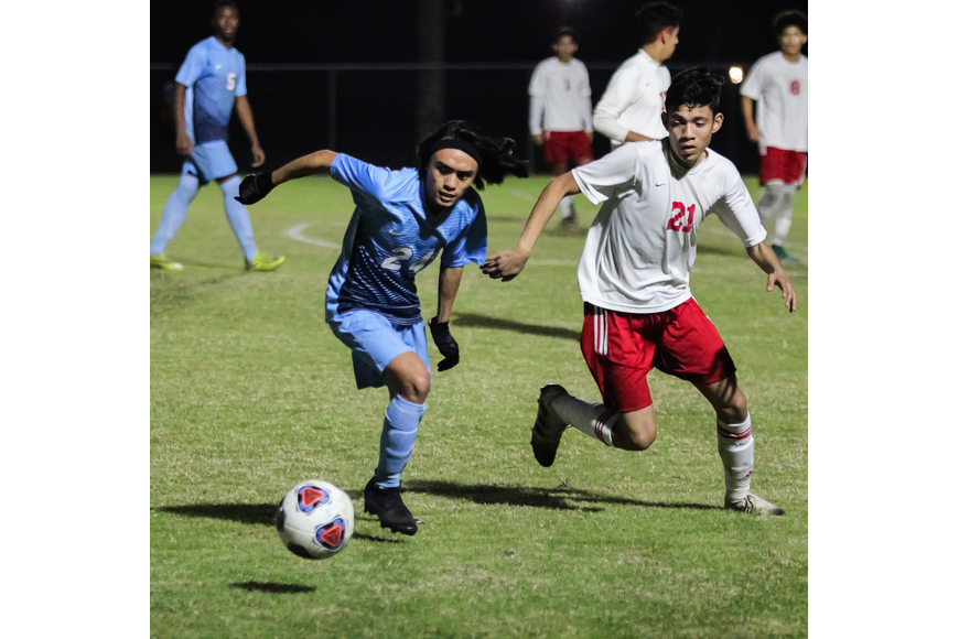 Eli Juezan chases after a loose ball against Taylor. Photo by Ray Boone