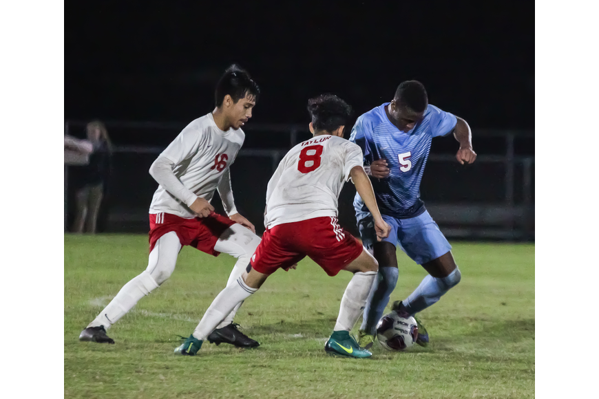 Seabreeze's Nate Thompson tries to keep the ball away from two Taylor defenders. Photo by Ray Boone