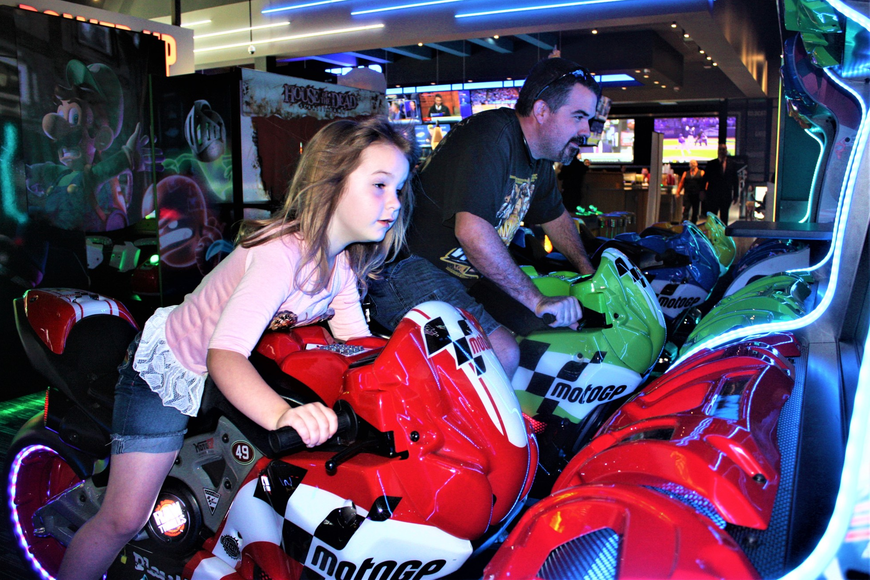 Priscilla Lent and her dad, Will, try out a motorcycle racing game at Dave and Buster's recently. Photo by Wayne Grant