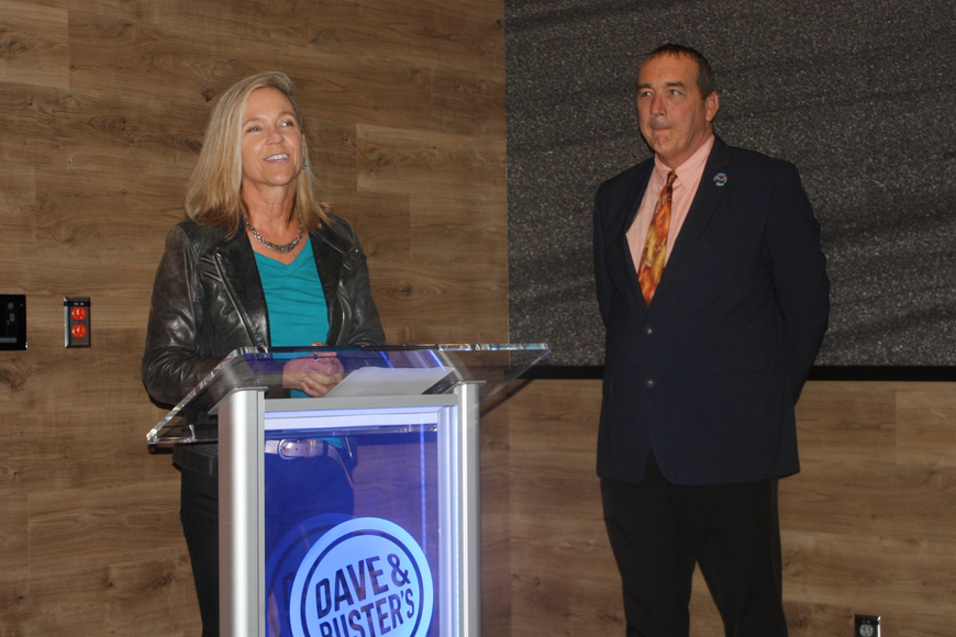 Lori Campbell Baker speaks at the ribbon cutting for Dave and Buster's, saying it will draw tourists. Also shown is General Manager Dave Joy. Photo by Wayne Grant
