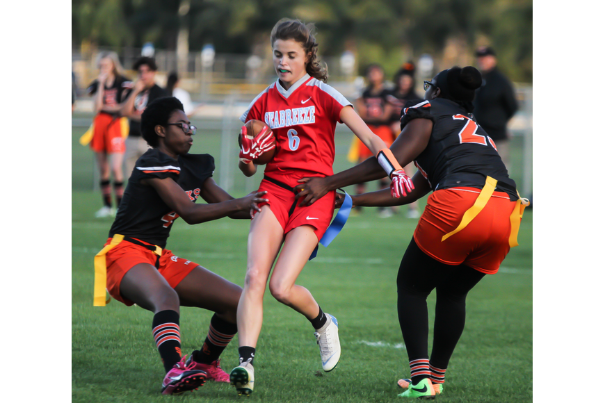 The Sandcrabs' Kara Haas rushes past two Hawks defenders. Photo by Ray Boone
