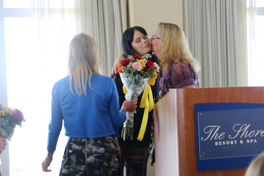 Emilee Cope's mother gives her a kiss after her speech at the Victims' Rights Week Breakfast & Awards Ceremony on Friday, April 12. Photo by Jarleene Almenas