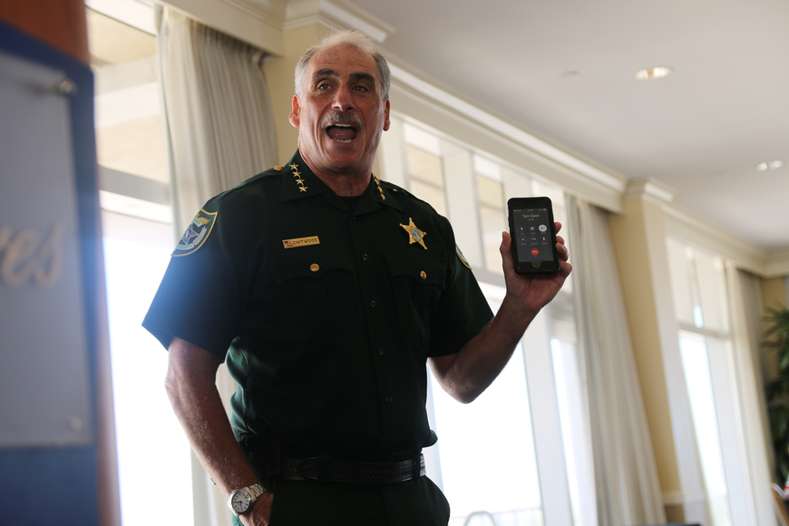 Volusia County Sheriff answers a phone call from Sgt. Thomas Dane, whose head was grazed by a gunshot yesterday while he and other deputies were trying to stop an armed carjacker in the DeLand area. Photo by Jarleene Almenas