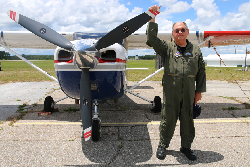 Lt. Col. Larry Fernald holds on to a plane's propeller at the Ormond Beach Municipal Airport. Photo by Jarleene Almenas