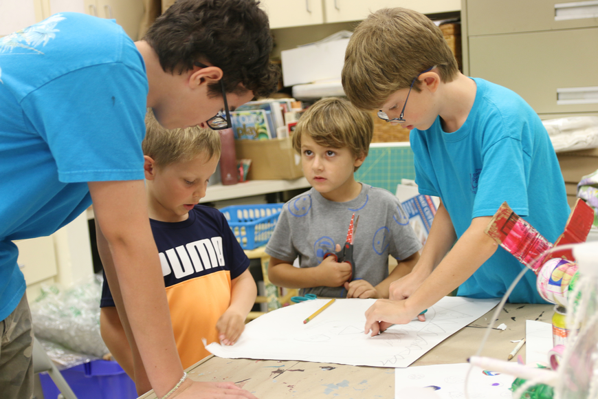 Camp Counselor Will Cross helps Luke Merkel, Henry Jones and Henry Graydon on their collaborative imagination mask during Re-Imaginarium Camp on Thursday, June 27. Photo by Jarleene Almenas