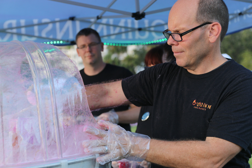 Andrew Van der Burgt, of O'Quinn Insurance, serves cotton candy during the Movies at the Halifax event at Rockefeller Gardens on Friday, Oct. 4. Photo by Jarleene Almenas