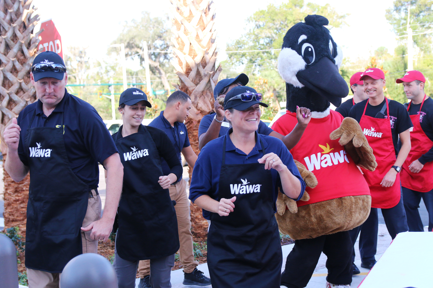 Ormond Beach Police Chief Jesse Godfrey, Sgt. Michelle Willis and Officer Cierra Devane dance with Wally Goose during the Wawa grand opening on Thursday, Oct. 17. Photo by Jarleene Almenas