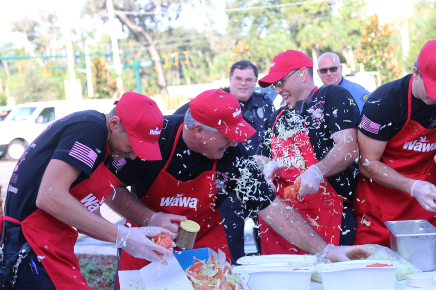 Firefighters Ethan Wilson, Dale Kelly, and Jeremiah Ingraham are hit with lettuce by the OBPD team during the Hoagies for Heroes contest. Photo by Jarleene Almenas