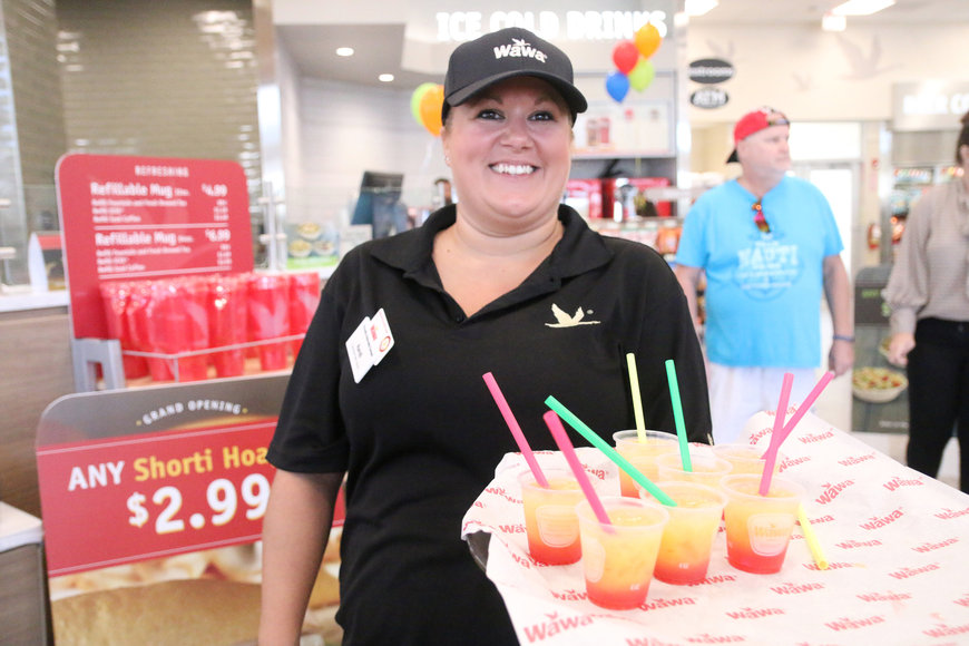 Wawa employee Randi Mott hands out free drink samples during the Wawa grand opening on Thursday, Oct. 17. Photo by Jarleene Almenas