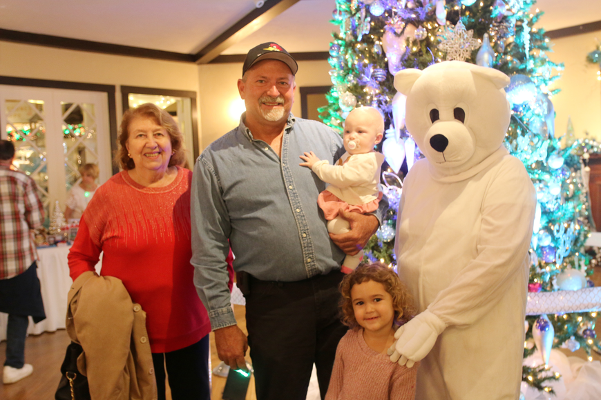 Joy and Robert Burk along with Kinsley and Maisyn Munson pose for a photo with the polar bear at the 41st-annual Christmas Gala at the Casements on Friday, Dec. 6. Photo by Jarleene Almenas