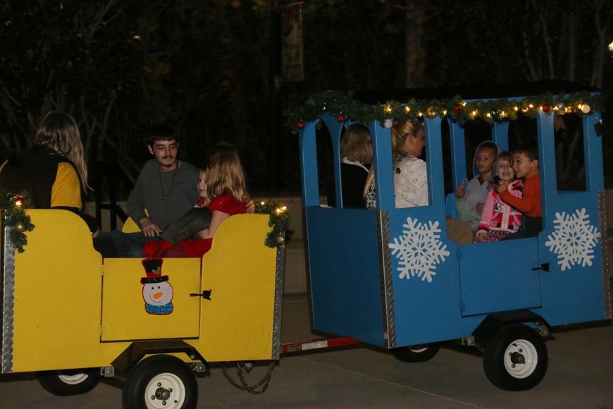 Families ride a train around Rockefeller Gardens during the 41st-annual Christmas Gala at the Casements on Friday, Dec. 6. Photo by Jarleene Almenas