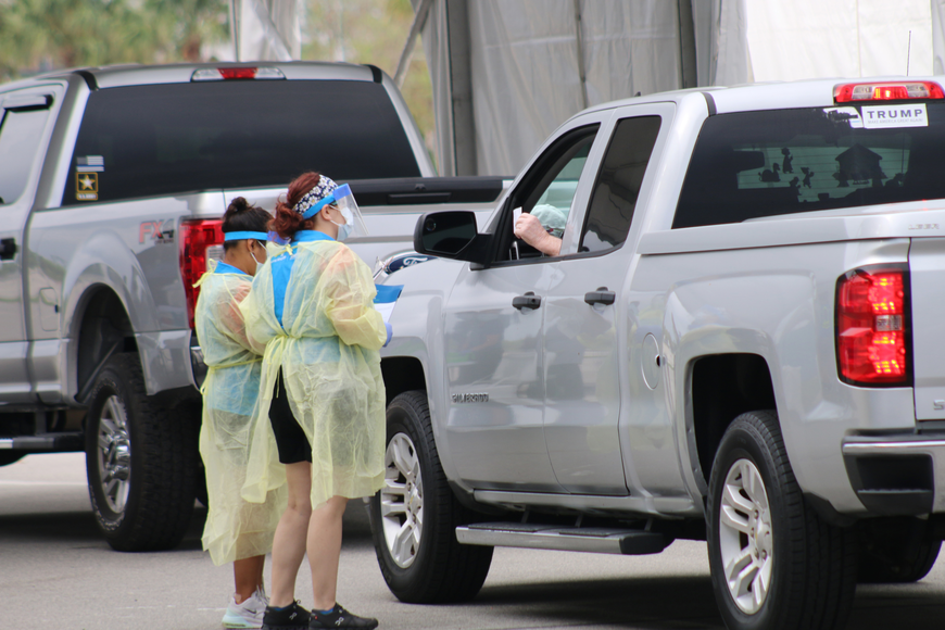 AdventHealth health care professionals speak with a person waiting to be tested at the new testing site at the Daytona International Speedway. Photo by Jarleene Almenas