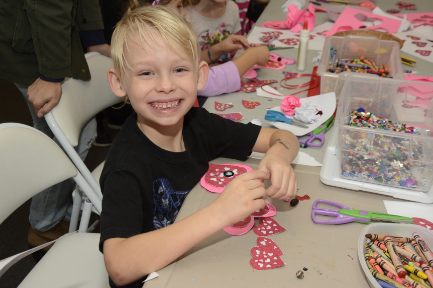 Noah Sparks, age 6, busies himself with gluing gems onto his paper hearts.